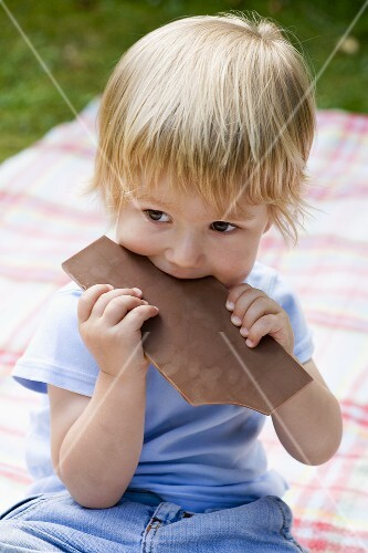 Boy biting into a bar of chocolate
