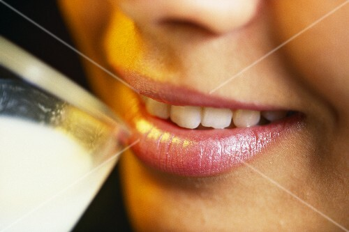 Woman putting glass of milk to her lips (detail)