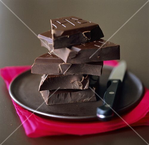 A pile of pieces of Valrhona chocolate on black plate