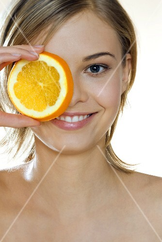 Young woman holding a slice of orange in front of her eye