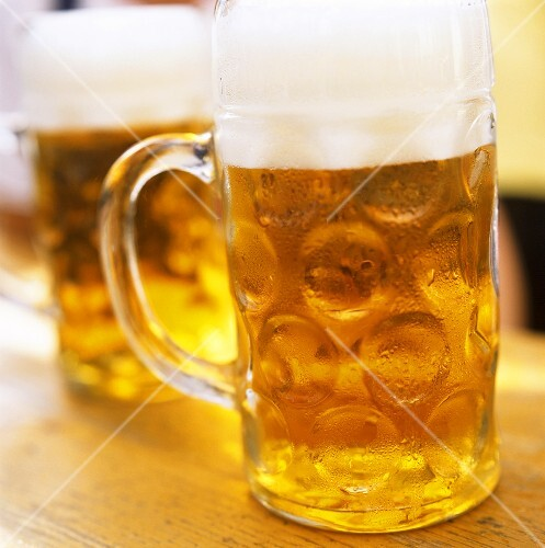 Two tankards of cold beer on a wooden table
