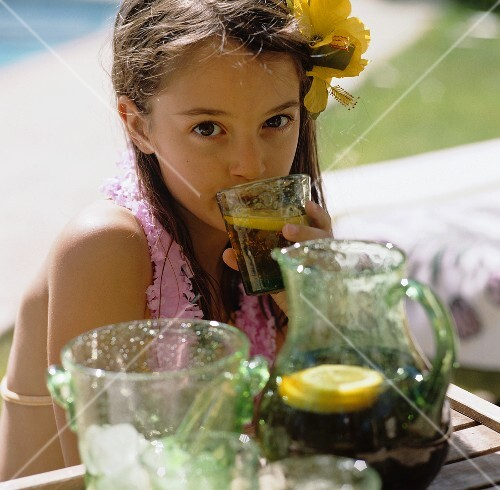 Girl drinking iced tea at a wooden table in open air