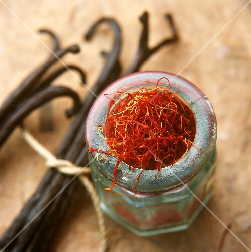 Saffron threads in a jar, vanilla pods beside it