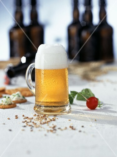 Cold beer in a glass tankard; Radish; Cracker; Beer bottles