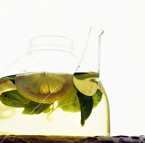 Tea with mint and lemon in glass pot
