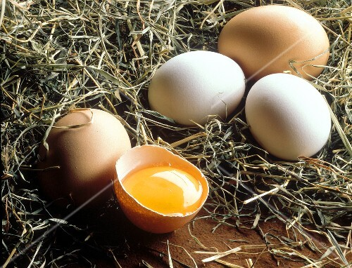 Brown and white eggs with a broken egg in hay