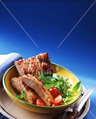 Spare-ribs with rocket and tomatoes