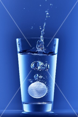 Effervescent tablet falling into a glass of water