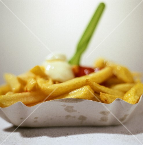 Chips with ketchup and mayonnaise in cardboard dish