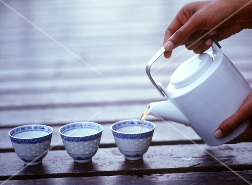 Pouring tea into Asian bowls