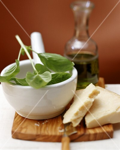 Still life with basil in mortar, Parmesan and olive oil