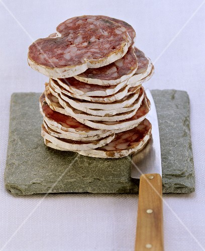 Farmhouse salami, sliced, on flat stone