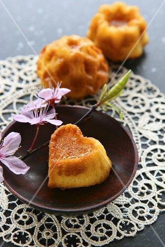 Small heart-shaped sponge cake with sprig of cherry blossom