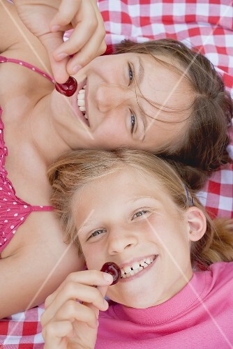 Two girls with cherries on a picnic cloth