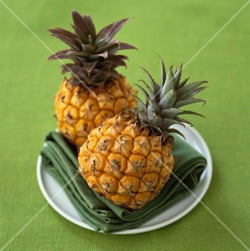 Two baby pineapples on a plate