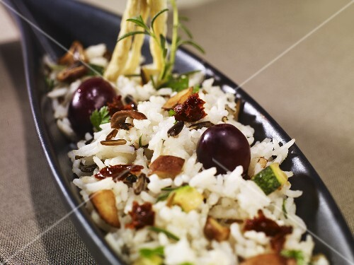 Rice dish with chestnut mushrooms, courgettes, black olives & dried tomatoes