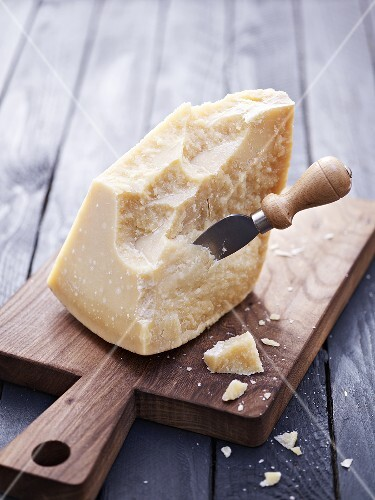 Piece of Parmesan cheese with cheese knife on chopping board