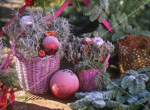 Pink baskets with Christmas decorations with hoar frost
