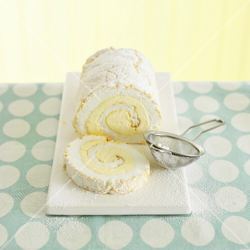Lemon meringue roulade with icing sugar, a slice cut
