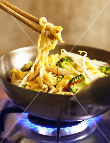 Noodles with chicken in wok on gas cooker