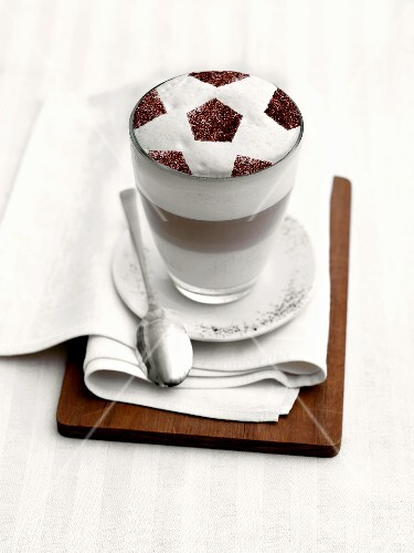 Latte macchiato with milk froth in football design