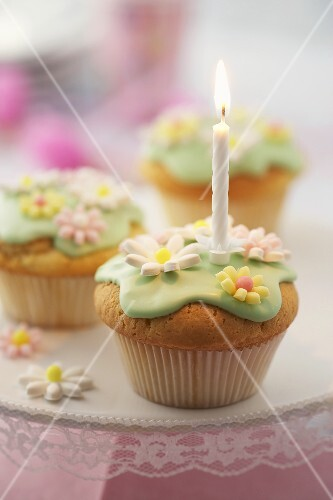 Birthday candle on muffin with sugar flowers
