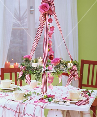 Hanging wreath of Douglas fir & roses above Christmas table