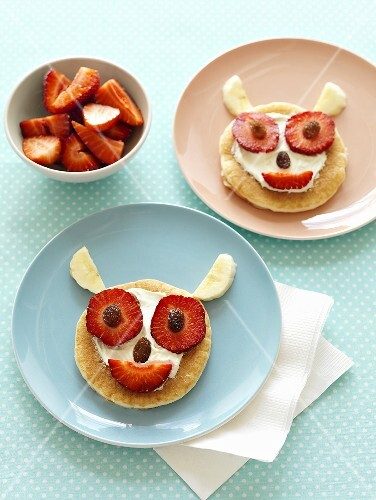 Amusing pancake faces with strawberries