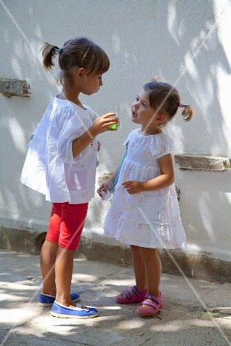 Two little girls with a glass of juice