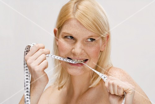 Blond woman biting tape measure