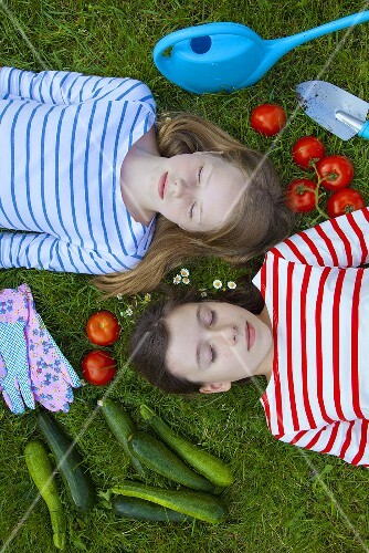 Two girls lying on the grass surrounded by vegetables