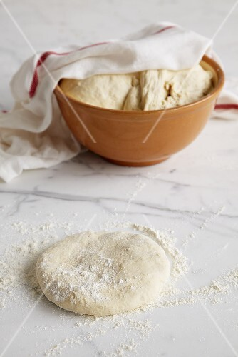 Pizza dough on marble slab and in bowl half-covered by tea towel