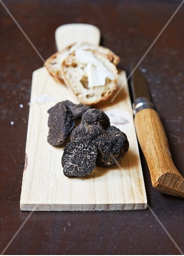 Black truffles on a wooden board