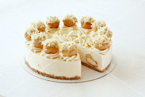 A cheesecake with profiteroles and white chocolate