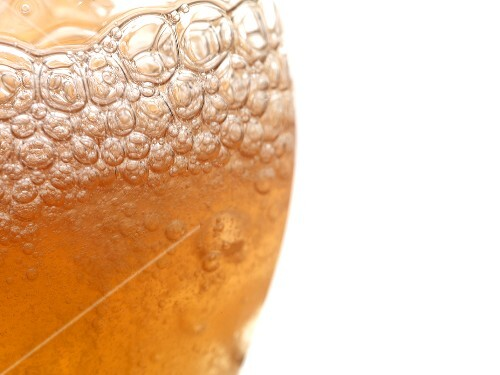 A glass of foamy cider (close-up)