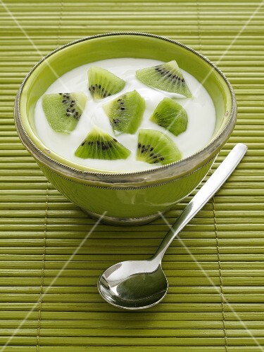 Natural yogurt with kiwis in a green bowl and spoon on the side