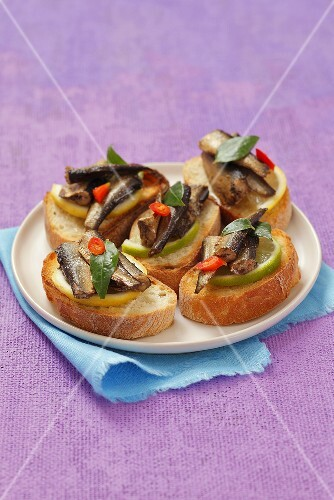 Toasted slices of baguette topped with smoked sprats