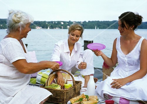 Three women unpacking a picnic basket on a landing stage