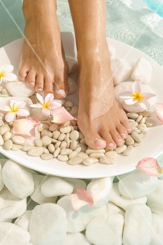 Feet on plate of stones and flowers in water