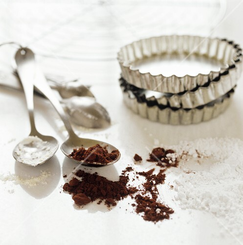 Baking utensils with cocoa and icing sugar