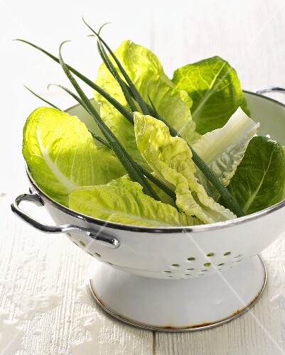Green salad and chives in a colander