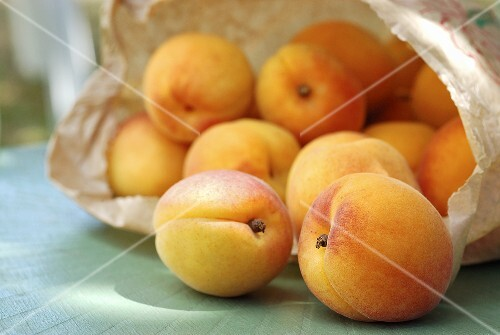 Apricots falling out of a paper bag
