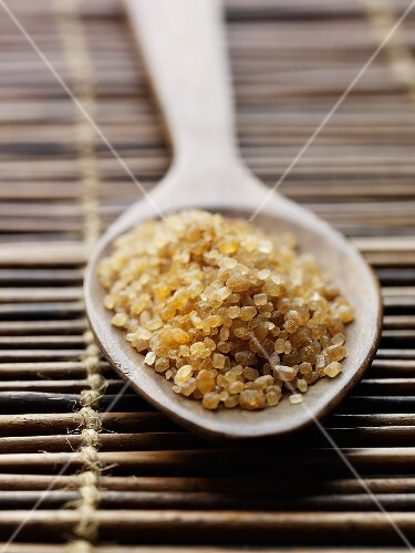 Raw cane sugar in a wooden spoon on a bamboo mat