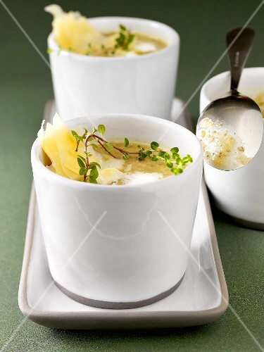 Lentil soup with thyme and cheese in two soup cups