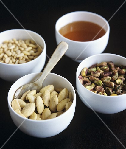 Pine nuts, almonds, pistachios and honey in small bowls