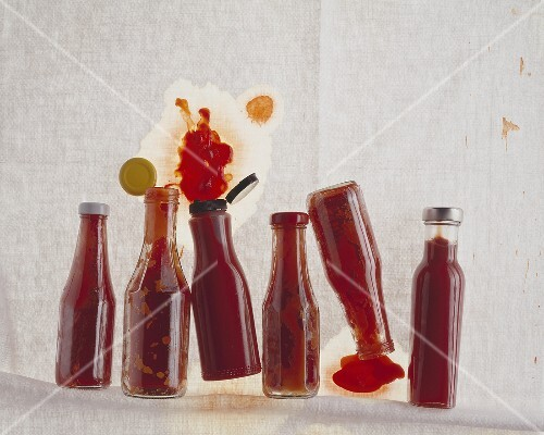 Several closed & opened ketchup bottles, lying on their sides