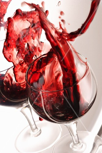 A glass of red wine spilling