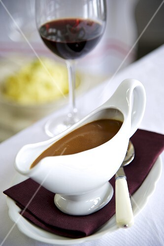 Gravy in a gravy boat with a glass of red wine in the background