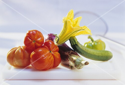 Washed tomatoes, courgette with flower and aubergine