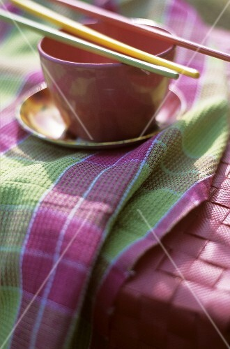 Bowl with chopsticks on coloured tea towel